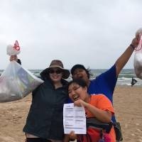 3 students showing the trash they have picked up and their tracking sheet